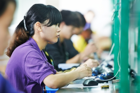industry electronic: female chinese worker woman testing production at line conveyor in china factory manufacturing Stock Photo