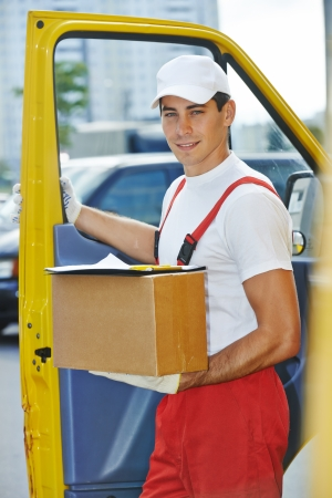 Postal delivery courier man in front of cargo van delivering package carton box photo