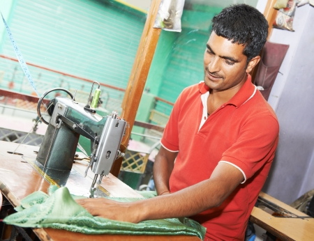 Portrait of indian man tailor at work place with sewing machine photo