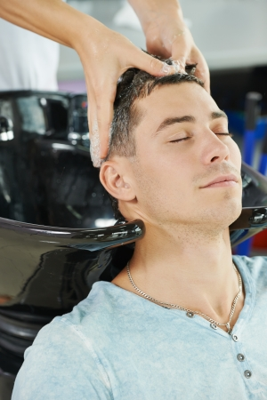salon: Washing man client hair in beauty parlour hairdressing salon Stock Photo