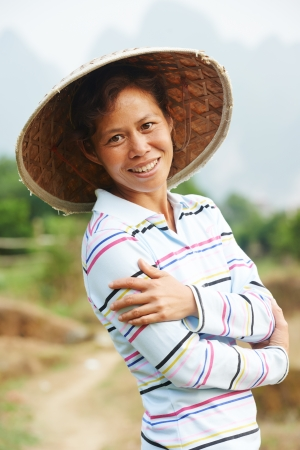 asian produce: Portrait of smiling chinese asian woman worker at farm work gathering citrus oranges in agriculture fruit garden Stock Photo