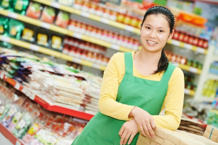 saleswomen: chinese young woman choosing food tea during shopping at china supermarket Stock Photo