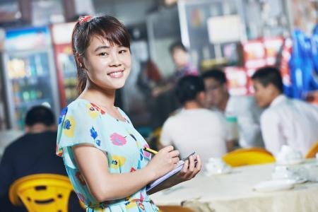 administrador de empresas: joven camarera china del restaurante de la calle en China con men� esperando una orden Foto de archivo