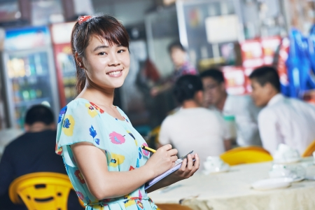 asia food: young Chinese waitress girl of street restaurant in china with menu waiting an order