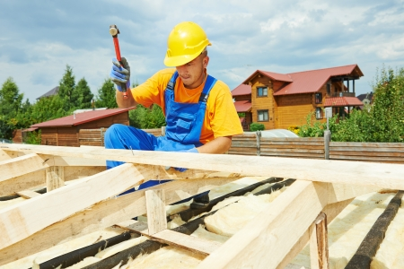 thatcher: roofer carpenter worker nailing wood board with hammer on roof installation work Stock Photo