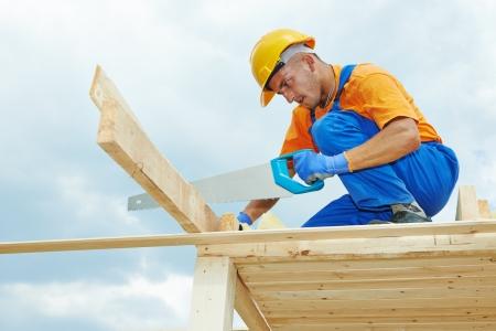 trussing: costruzione conciatetti carpentiere operaio taglio tavola di legno con la sega a mano a lavori di installazione sul tetto