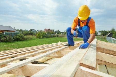 bouw dakdekker timmerman werknemer hameren houten bord met hamer en spijker op het dak installatiewerk
