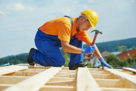 建設屋根葺き職人大工ワーカー釘付け木板の屋根の取付けにハンマーでの作業します。 写真素材
