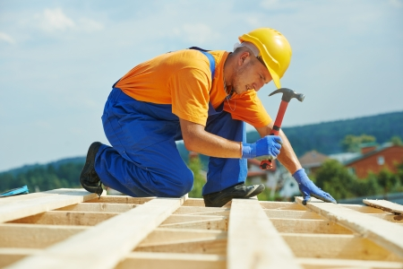 construction helmet: construction roofer carpenter worker nailing wood board with hammer on roof installation work Stock Photo