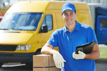Lachende jonge mannelijke postbezorging courier man tegenover bestelwagen leveren pakket