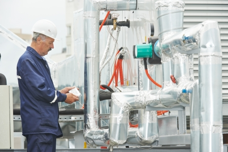 building maintenance: adult electrician engineer working with ventilation and conditioning system