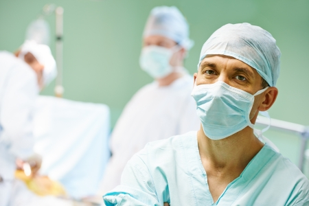 Portrait of surgeon medic in front of surgeons perfoming operation on a patient at cardiac surgery clinic Stock Photo - 22011394