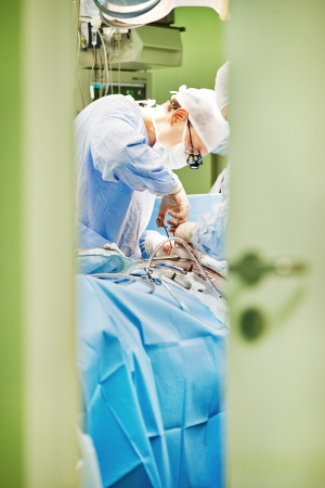 surgeon in uniform perform operation on a patient at cardiac surgery clinic photo
