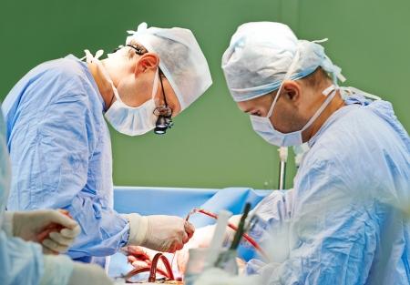 interventie: Twee chirurg in uniform voeren operatie op een patiënt bij cardiale chirurgie kliniek Stockfoto