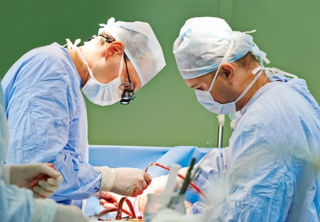 Two surgeon in uniform perform operation on a patient at cardiac surgery clinic