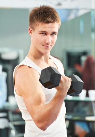 bodybuilder man at biceps brachii muscles exercises with training dumbbells in fitness gym photo