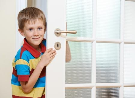 abriendo puerta: Niña que abre la puerta blanca en el hogar niño sonriente