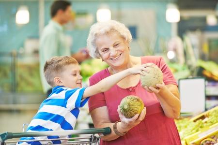 внук: Взрослая женщина с ребенком выборе дыни плоды во время покупки в растительном супермаркете Фото со стока