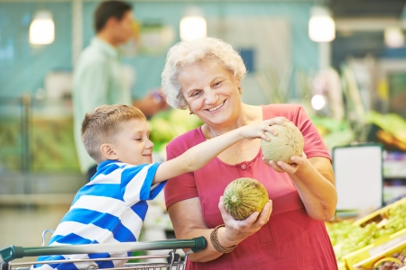 Adult woman with child choosing melon fruit during shopping at vegetable supermarket