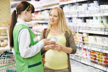 vendedor: Asistente de ventas en supermercados demostrando productos lácteos comida clienta embarazada durante las compras en una tienda