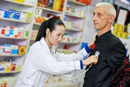 chinese pharmacist chemist woman examining heartbeat of customer in china pharmacy drugstore photo