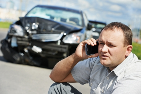 Adult upset driver man discussing on mobile phone in front of automobile crash car collision accident in city road photo