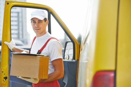 order delivery: delivery courier man in front of cargo van delivering package carton box Stock Photo