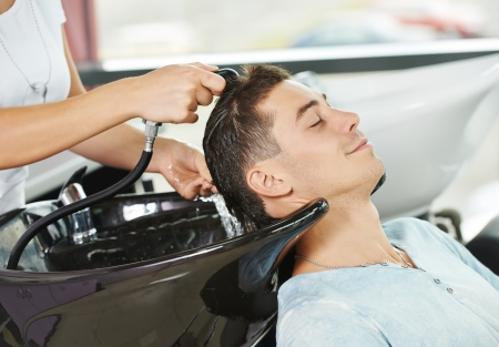 parlour: Washing man client hair in beauty parlour hairdressing salon Stock Photo