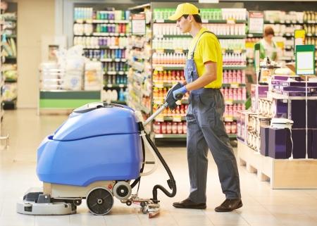 mujer limpiando: Cuidado de los pisos y los servicios de limpieza con lavadora en tienda tienda supermercado Foto de archivo