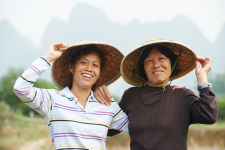 asian produce: Smiling chinese asian women workers at farm work gathering citrus oranges in agriculture fruit garden