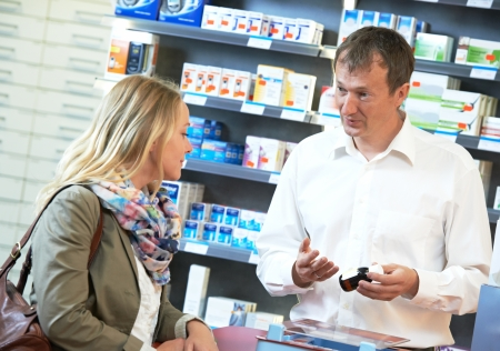 cheerful pharmacist chemist man worker standing at pharmacy drugstore desk with colleague Stock Photo - 22086523
