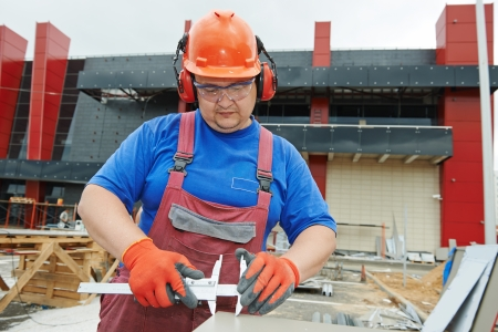 workplace safety: Builder worker with caliper measure plastic parts at construction site Stock Photo