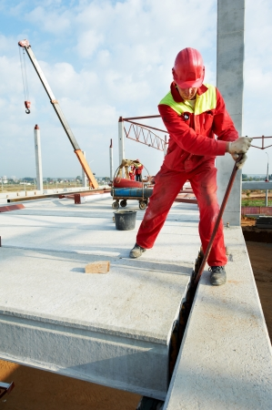 foremaster: builder worker in safety protective equipment installing concrete floor slab panel at building construction site Stock Photo
