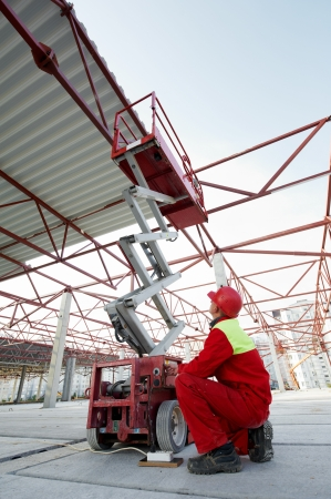 roof framework: builder worker operating wth lift machine equipment at metal construction framework installation
