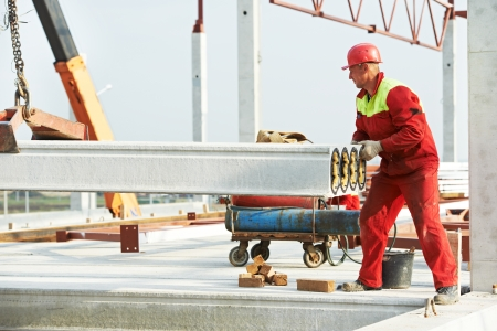 concrete in construction: builder worker in safety protective equipment installing concrete floor slab panel at building construction site Stock Photo