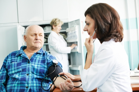 arterial: doctor measuring blood pressure of patient by phonendoscope in clinic hospital Stock Photo