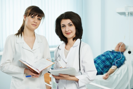 Two young female doctor in medic uniform with stethoscope in hospital clinic during examination photo