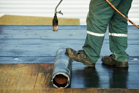 Dakdekker installeren Dakleer met verwarming en smelten van bitumen roll door toorts op vlam tijdens het dak te repareren Stockfoto