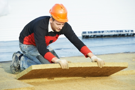 roofer: Roofer builder worker installing roof insulation material Stock Photo