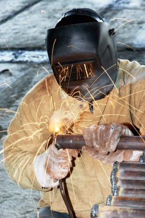 welder worker welding metal by electrode with bright electric arc and sparks during manufacture of metal equipment photo
