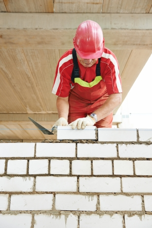 Builder construction mason worker bricklayer installing brick with trowel putty knife outdoors photo