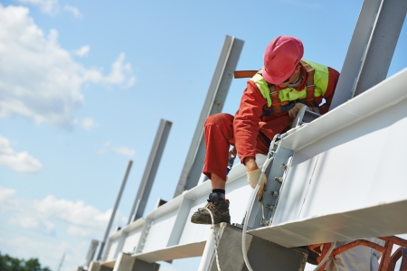 millwright: worker in uniform and safety protective equipment at metal construction frames installation and assemblage
