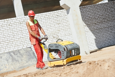 roadwork: builder worker compacting soil with vibration plate compaction machine during pavement roadwork