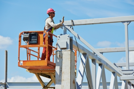 erector: worker in uniform and safety protective equipment at metal construction frames installation and assemblage