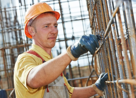 builder worker knitting metal rods bars into framework reinforcement for concrete pouring at construction site Stock Photo - 22224311