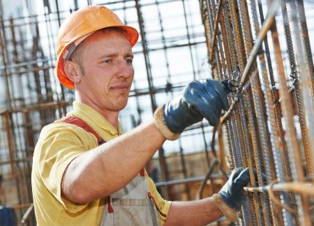 obreros trabajando: trabajador de construcci�n que hace punto del metal en barras barras de refuerzo marco para el vertido del hormig�n en obra en construcci�n