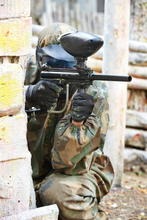 paintball player in protective uniform and mask aiming gun before shooting in summer photo