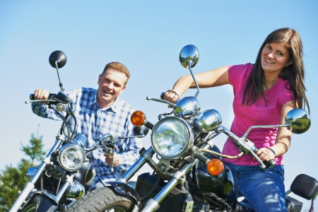 Happy smiling young man and woman couple together sitting on motorbikes outdoors photo