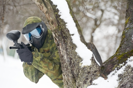 paintball: paintball extreme sport player in protective mask and comouflage clothing with marker gun at winter outdoors