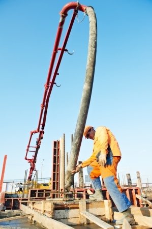 vibration machine: builder worker standing near trailer-mounted boom concrete pump on metal rods reinforcement of concrete casting formwork